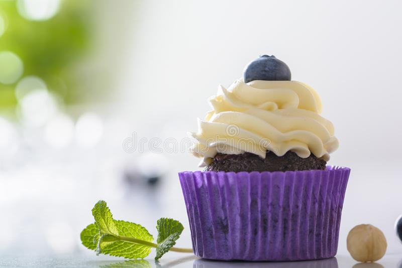 Petit gâteau avec la myrtille, la noisette et les feuilles en bon état dans l'enveloppe pourpre sur le dessus de table de marbre  image libre de droits