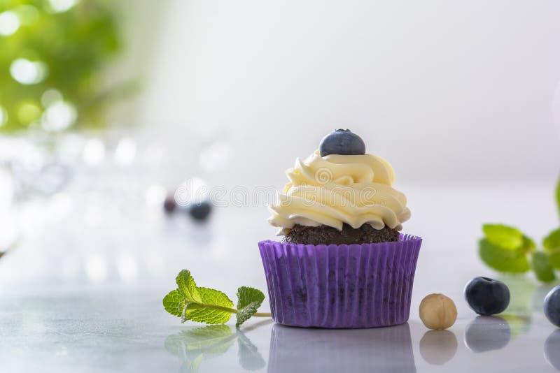 Petit gâteau avec la myrtille, la noisette et les feuilles en bon état dans l'enveloppe pourpre sur le dessus de table de marbre  photo libre de droits