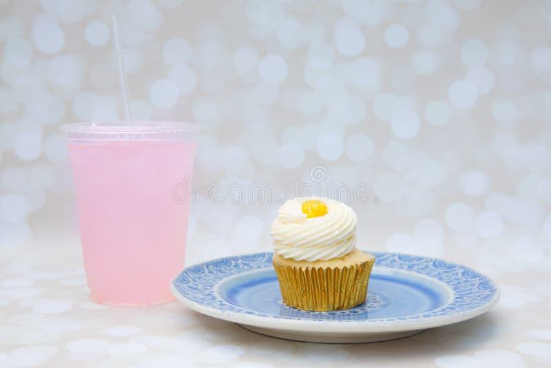 Petit gâteau avec le lait caillé et le glaçage de citron d'un plat et d'une limonade rose pour un ensemble de casse-croûte image stock
