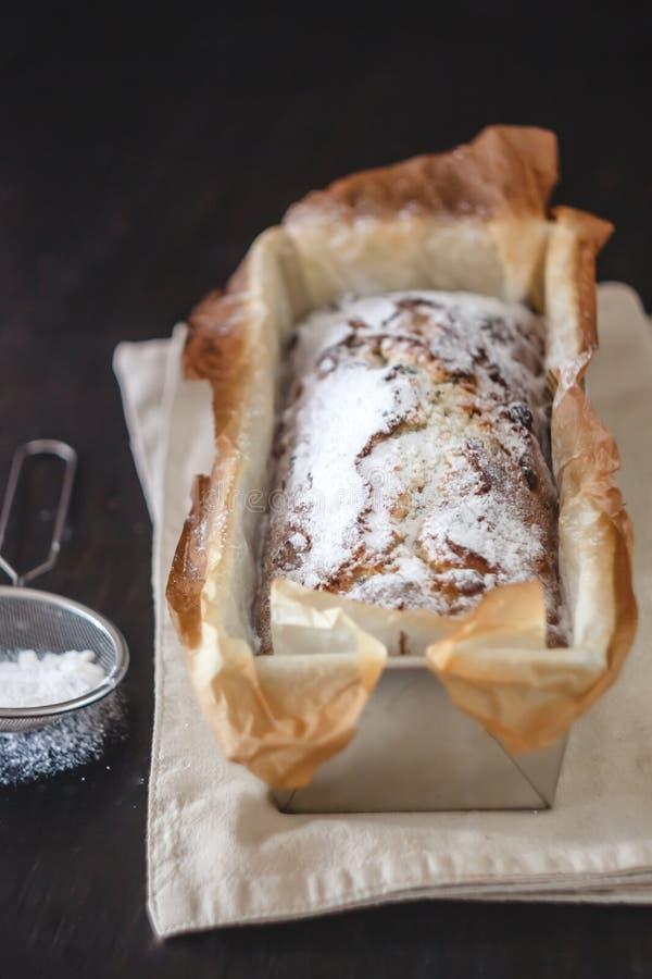 Petit gâteau capital rectangulaire avec du sucre en poudre dans un plat de cuisson en métal sur un fond foncé Plan rapproch? Vue  images stock