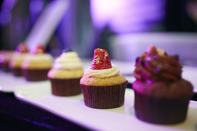 Petit gâteau coloré de tasse en nourriture de buste de tir étroit de plat photo libre de droits