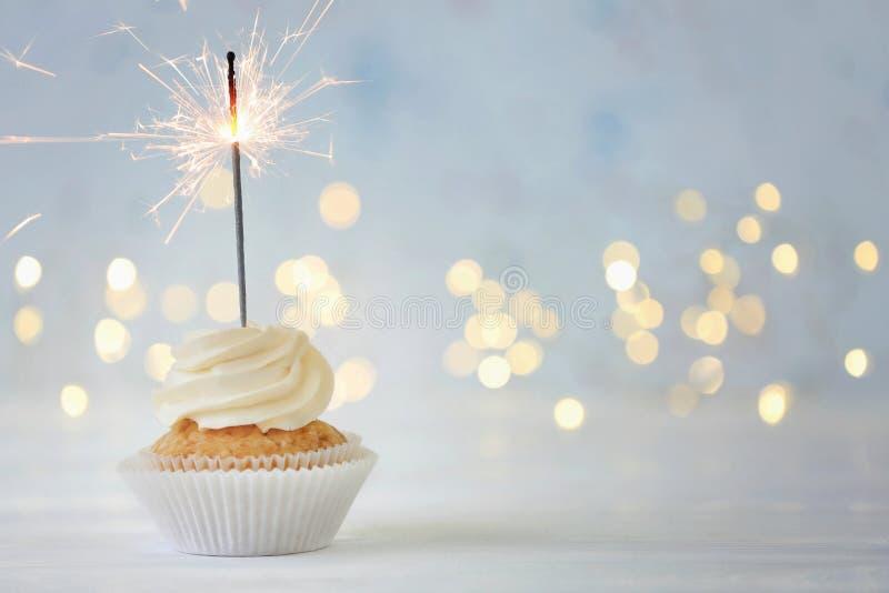 Petit gâteau délicieux avec le cierge magique sur la table blanche contre les lumières brouillées image libre de droits