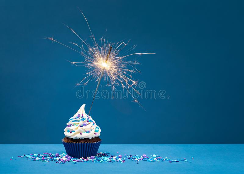 Petit gâteau d'anniversaire sur le bleu avec le cierge magique image libre de droits