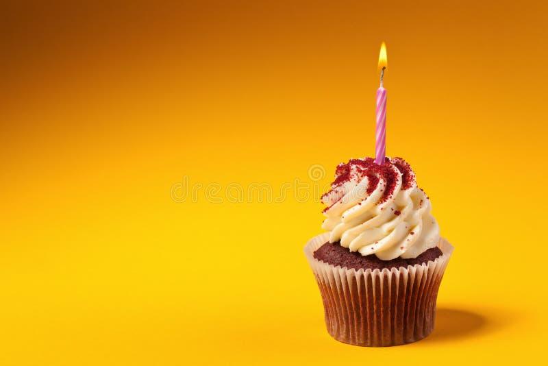 Petit gâteau de chocolat avec la bougie sur le fond orange image libre de droits