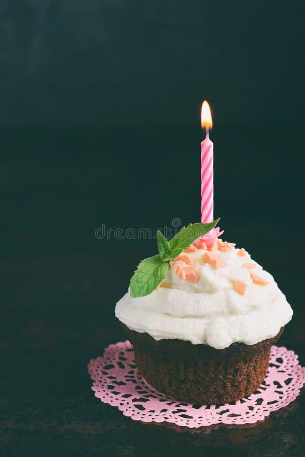Petit gâteau de chocolat avec de la crème et la bougie de vanille Joyeux anniversaire Photo foncée image libre de droits