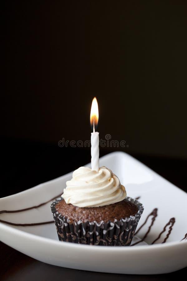 Petit gâteau de chocolat avec une bougie brûlante d'anniversaire images libres de droits