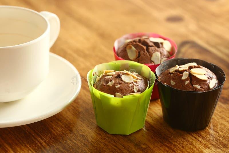 Petit gâteau de chocolat et de noisette sur la table avec du Cu blanc de thé photos stock