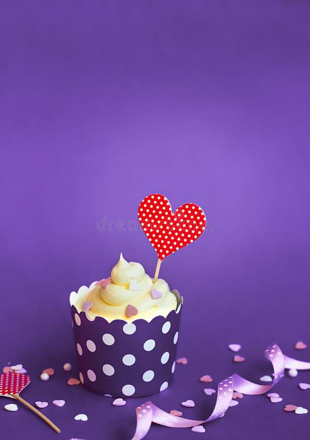 Petit gâteau de vanille avec de petits coeurs décoratifs et toppe rouge de coeur photos libres de droits
