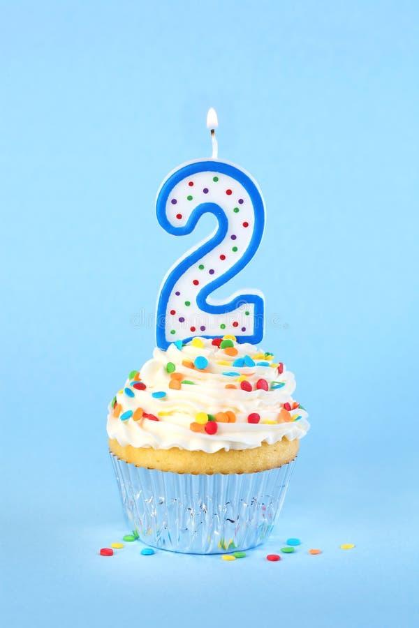 Petit gâteau glacé d'anniversaire avec avec le numéro allumé 2 bougies photo stock