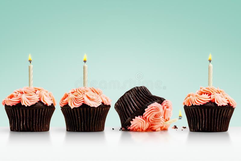 Petit gâteau laissé tomber dans la rangée des petits gâteaux avec des bougies sur le vert photo stock