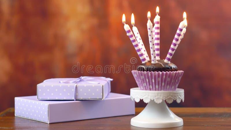 Petit gâteau pourpre d'anniversaire de thème avec les bougies et le cadeau photographie stock libre de droits