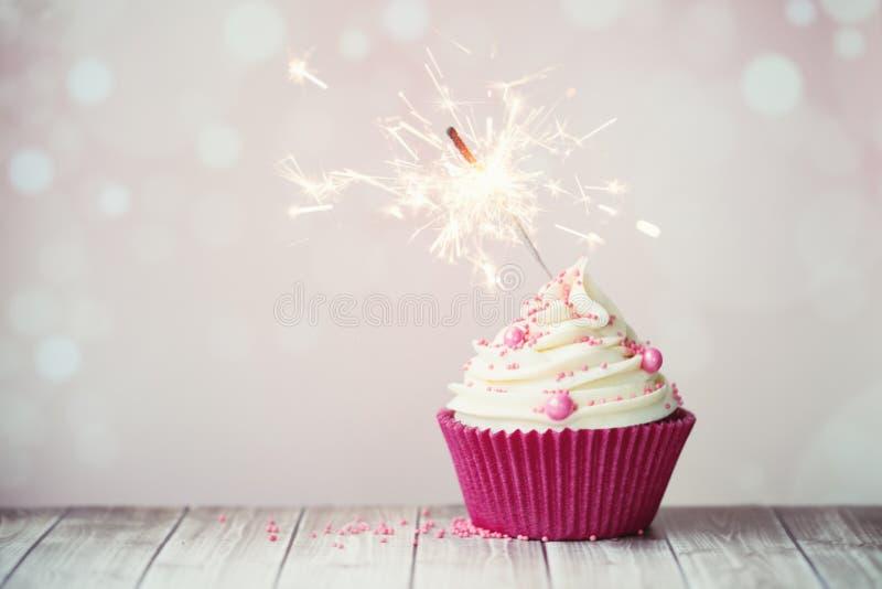 Petit gâteau rose avec le cierge magique images libres de droits