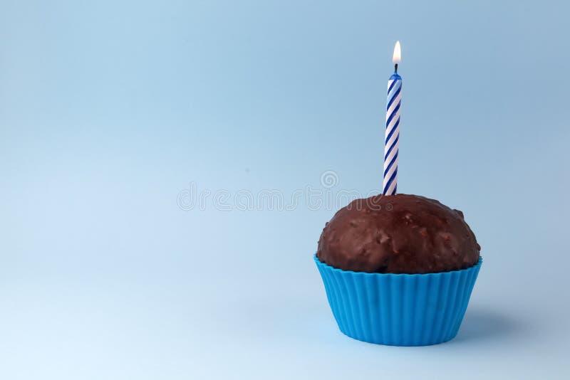 Petit gâteau savoureux d'anniversaire avec la bougie, sur le fond bleu, avec l'espace libre photographie stock libre de droits