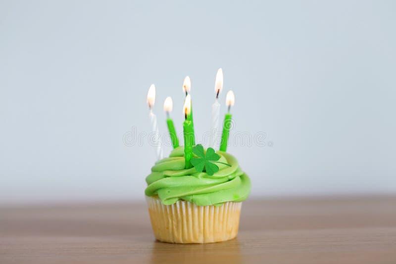 Petit gâteau vert avec six bougies brûlantes sur la table image stock