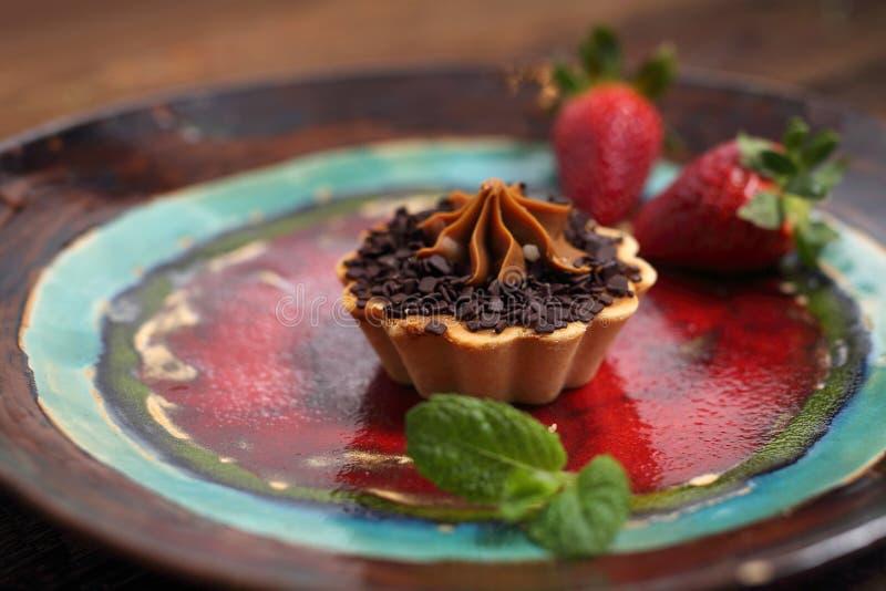 Petit g?teau de chocolat sucr? avec de la cr?me Dessert doux servi avec le fruit de fraise photographie stock