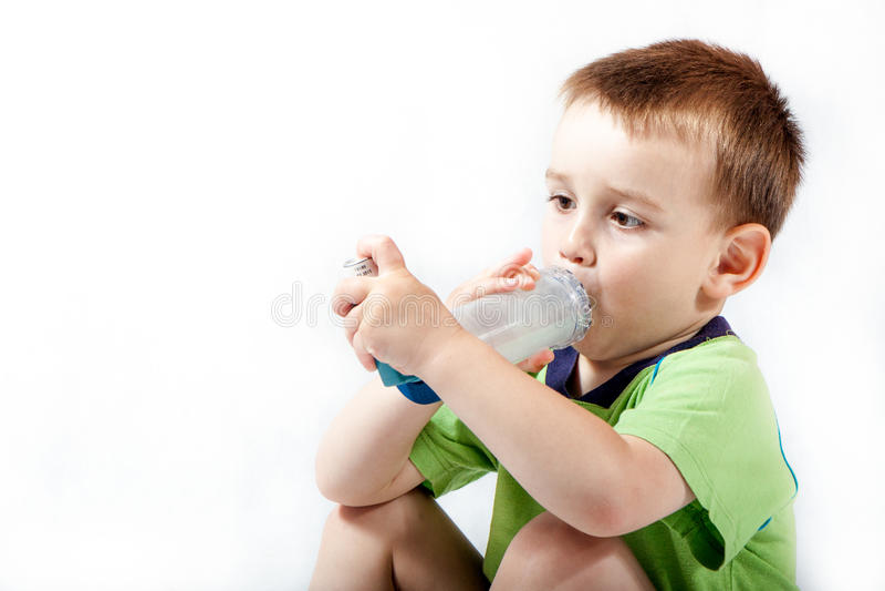Petit garçon à l'aide de l'inhalateur pour l'asthme photos libres de droits