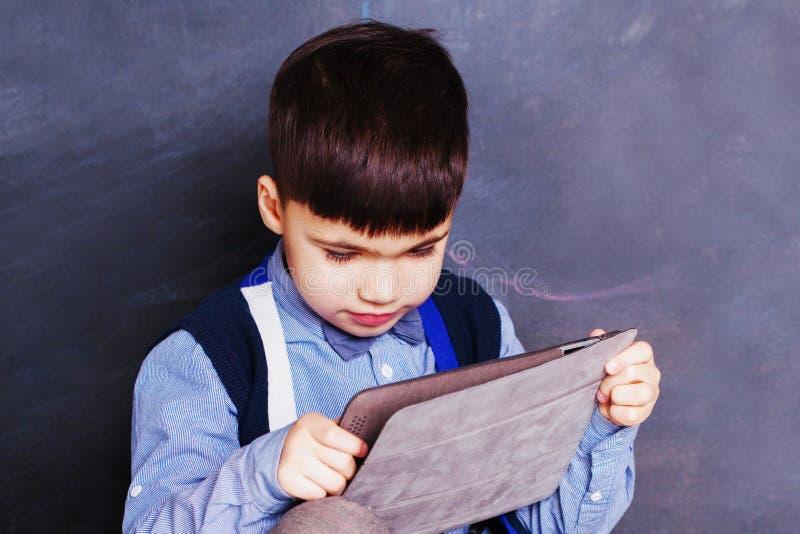 Petit garçon à l'aide du comprimé à la maison image libre de droits