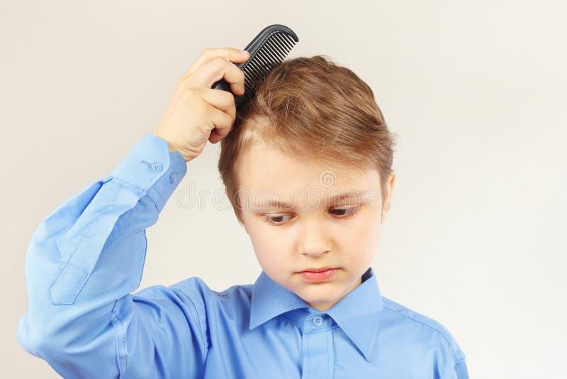 Download Petit Garçon élégant Dans Le Peigne Lumineux De Chemise Une Brosse à Cheveux Photo stock - Image du enfant, innocence: 76087928