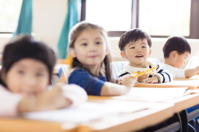 petit garçon étudiant dans la salle de classe photo libre de droits