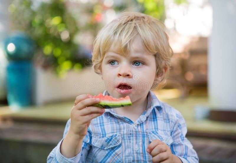 Petit garçon adorable d'enfant en bas âge avec les poils blonds mangeant la pastèque i photo libre de droits