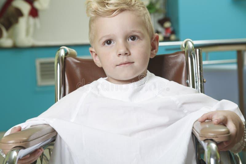 Petit garçon adorable dans le fauteuil roulant au photos stock