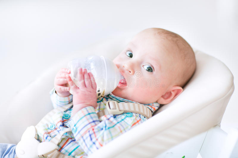 Petit garçon adorable s'asseyant en lait dringing de chaise d'arbitre photographie stock