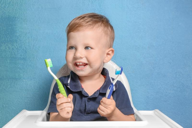Petit garçon adorable tenant deux brosses à dents photo libre de droits