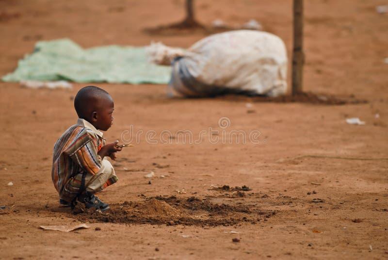 Petit garçon africain s'accroupissant photographie stock libre de droits