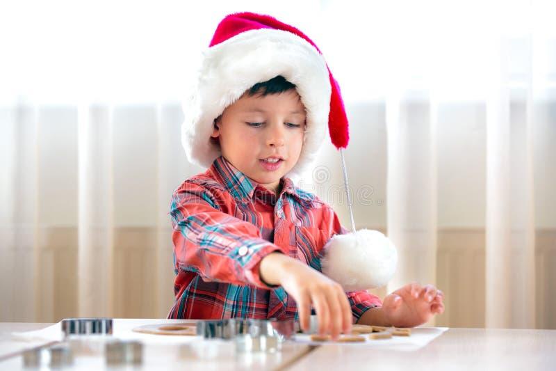 Petit garçon aidant à la cuisine avec des biscuits de traitement au four photographie stock libre de droits