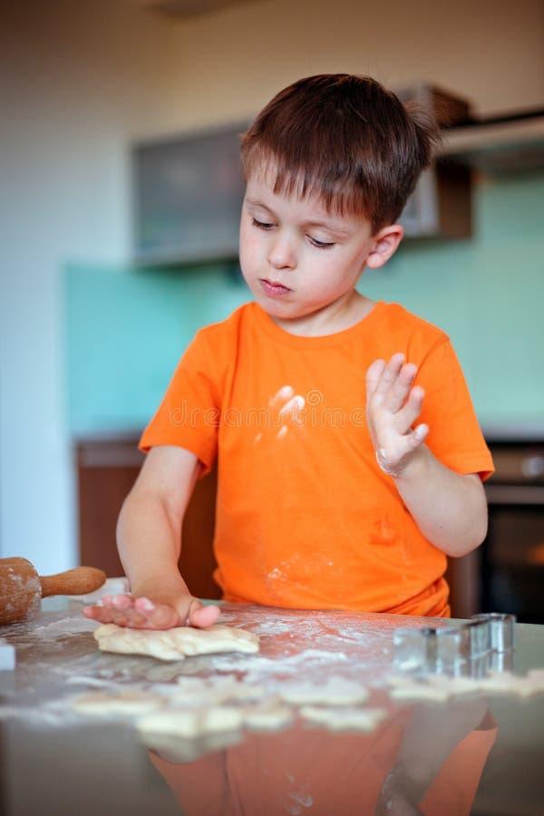 Petit garçon aidant avec des biscuits de cuisson images libres de droits