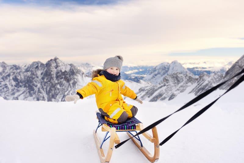 Petit garçon appréciant un tour de traîneau Badine le traîneau dans les montagnes d'Alpes en hiver images libres de droits