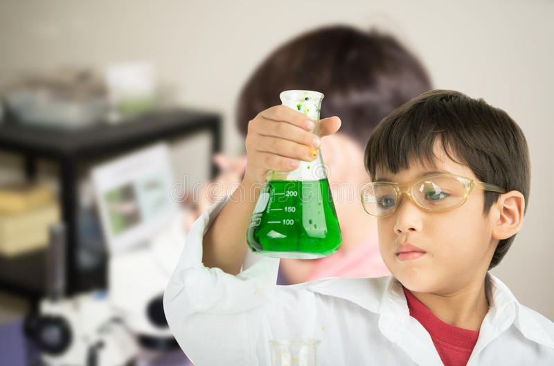 Petit garçon apprenant dans chemecal en science dans la classe photographie stock libre de droits