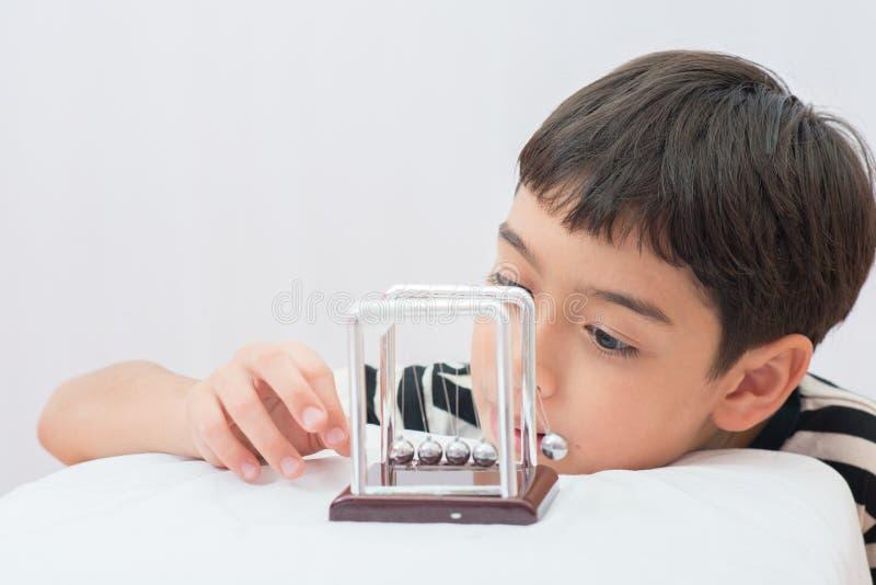 Petit garçon apprenant la boule d'équilibre de newton pour le médicament de la science photographie stock