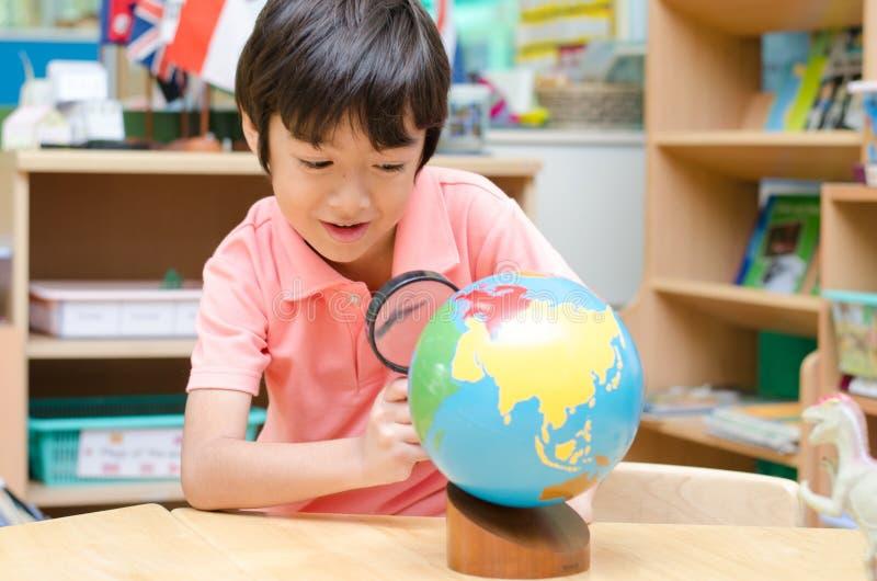 Petit garçon apprenant la carte dans la salle de classe images libres de droits
