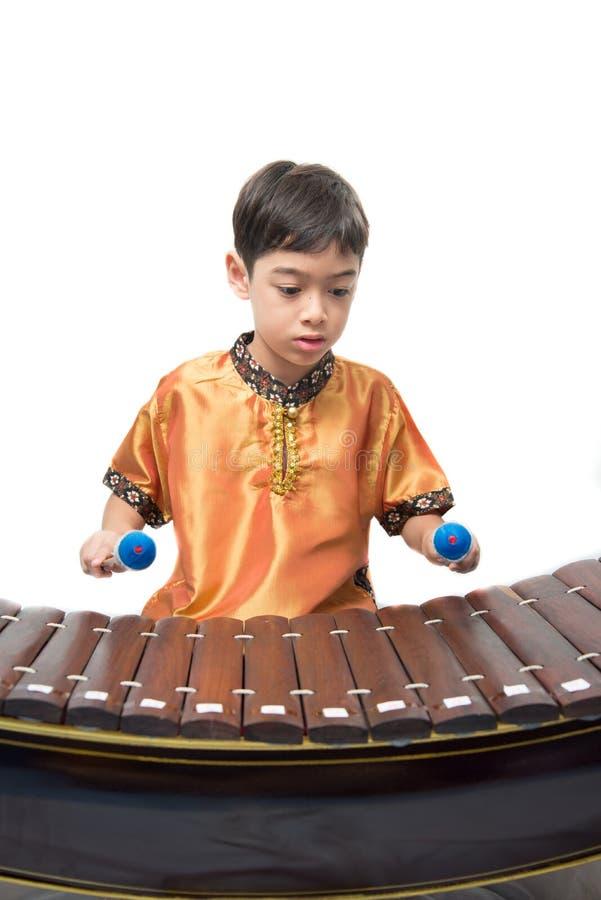 Petit garçon apprenant le xylophone thaïlandais d'instument, Ranat, sur le fond blanc image stock