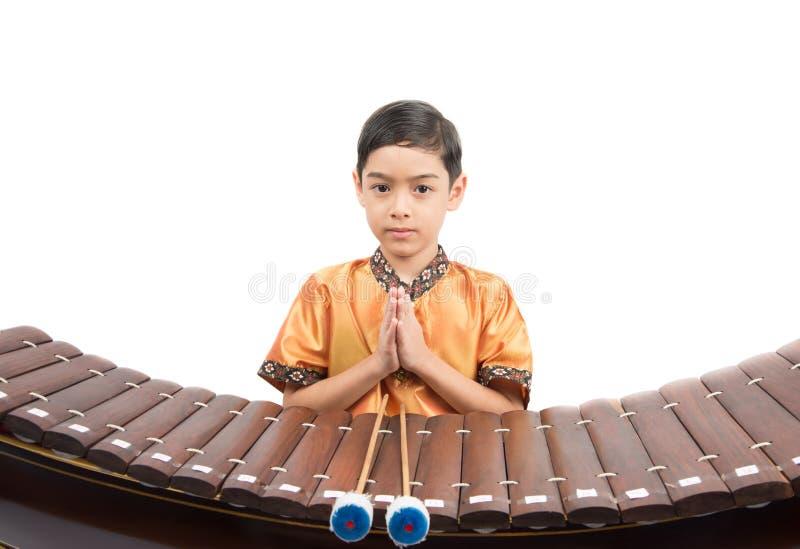 Petit garçon apprenant le xylophone thaïlandais d'instument, Ranat, sur le fond blanc image libre de droits