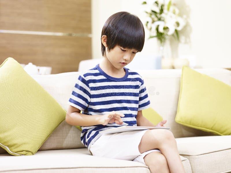 Petit garçon asiatique à l'aide du comprimé numérique photographie stock
