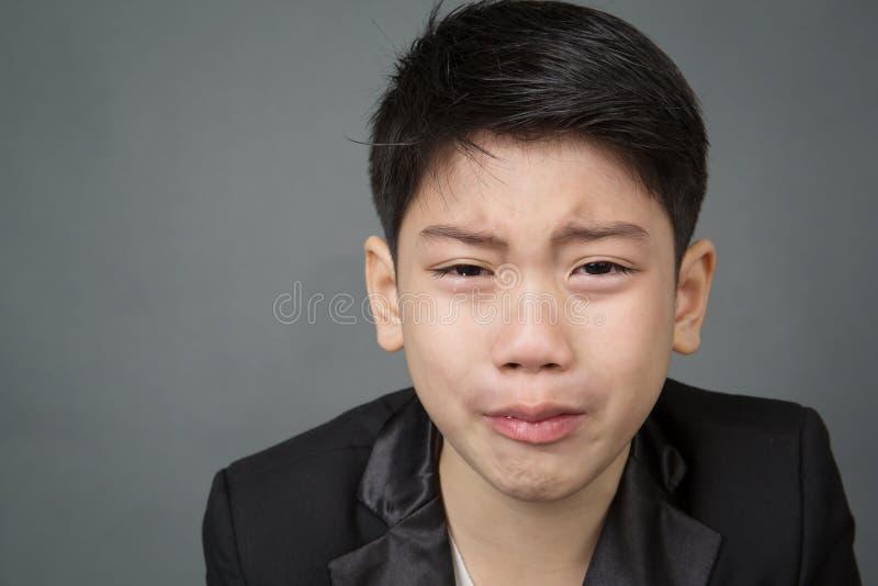 Petit garçon asiatique dans le renversement noir de costume, visage de dépression photo libre de droits