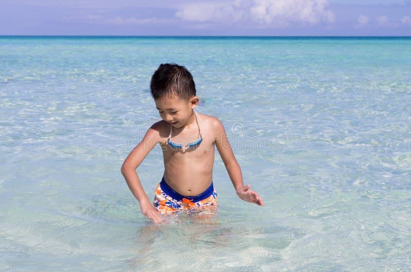 Petit garçon asiatique mignon jouant avec de l'eau en bleu turquoise images stock