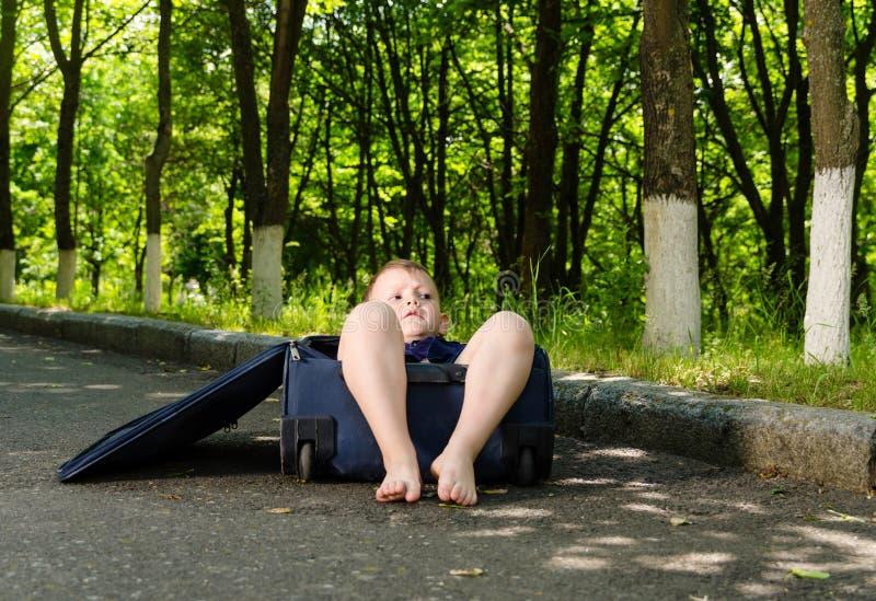 Petit garçon aux pieds nus à l'intérieur d'une valise photos libres de droits
