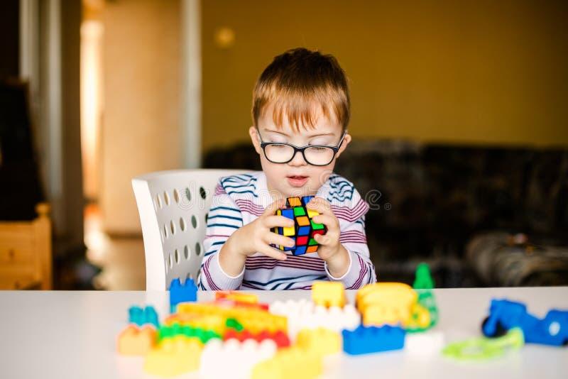 Petit garçon avec l'aube de syndrome dans les verres noirs jouant avec des blocs photos stock