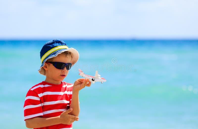 Petit garçon avec l'avion de jouet à la plage, concept de voyage images stock