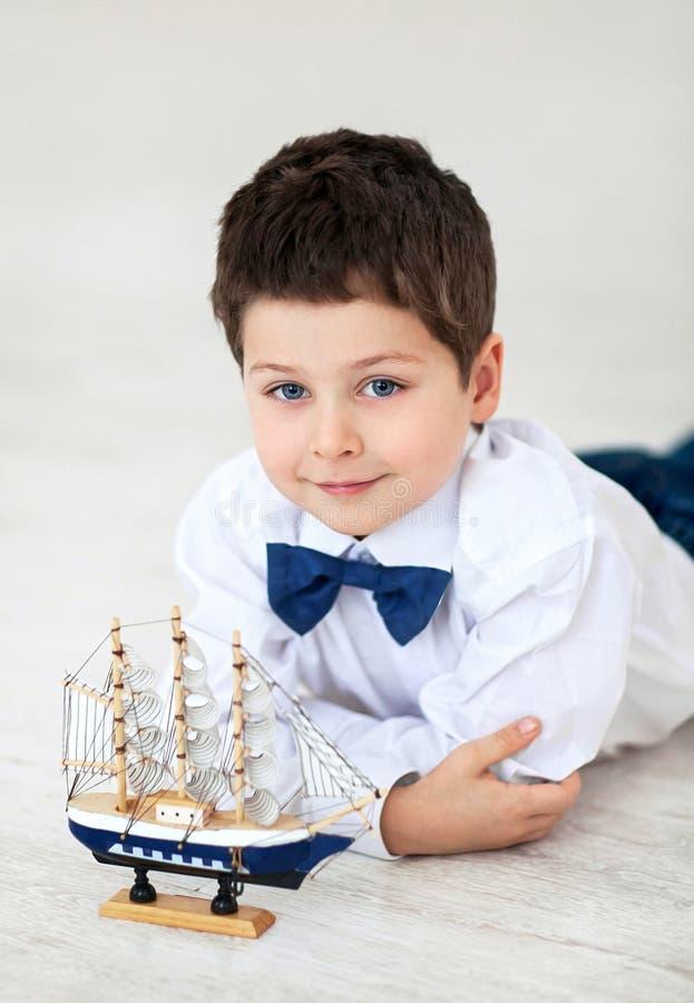 Petit garçon avec le bateau image stock