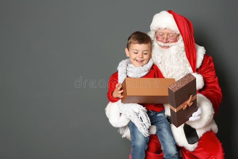 Petit garçon avec le boîte-cadeau se reposant sur le recouvrement authentique de ` de Santa Claus sur le fond gris photographie stock
