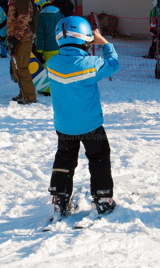 Petit garçon avec le casque après le ski un jour ensoleillé photo libre de droits