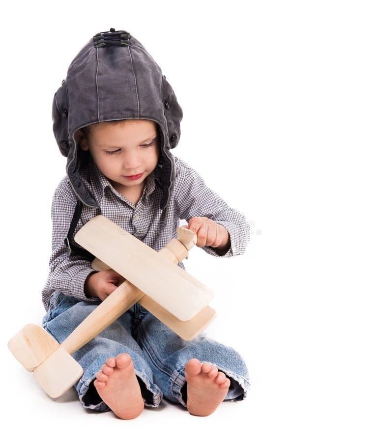 Petit garçon avec le chapeau pilote jouant l'avion de jouet photos libres de droits