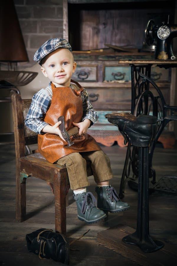 Petit garçon avec le marteau imitant le cordonnier image libre de droits