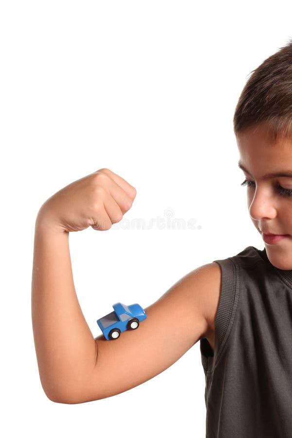 Petit garçon avec le véhicule de jouet sur le muscle photographie stock libre de droits