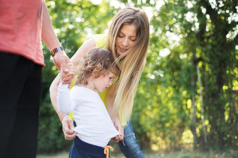Petit garçon avec ses parents en nature ensoleillée verte d'été photo stock