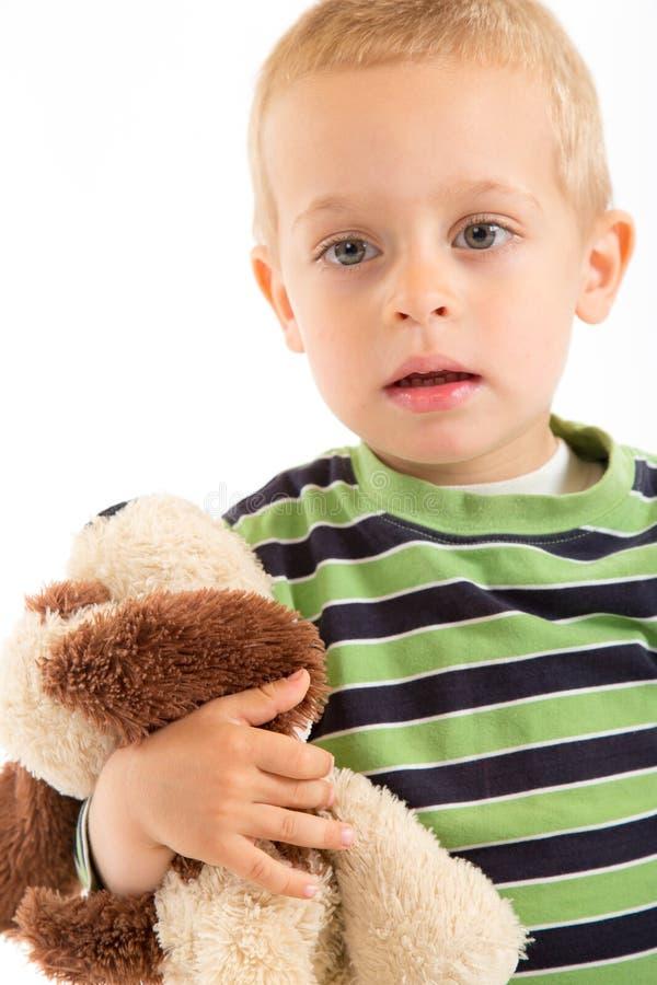 Petit garçon avec son chiot de peluche D'isolement sur le blanc photo stock